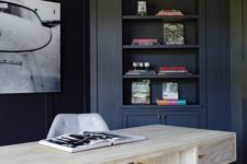 a contrasting home office with navy walls and built-in furniture, a bleached wooden desk and a statement artwork on the wall