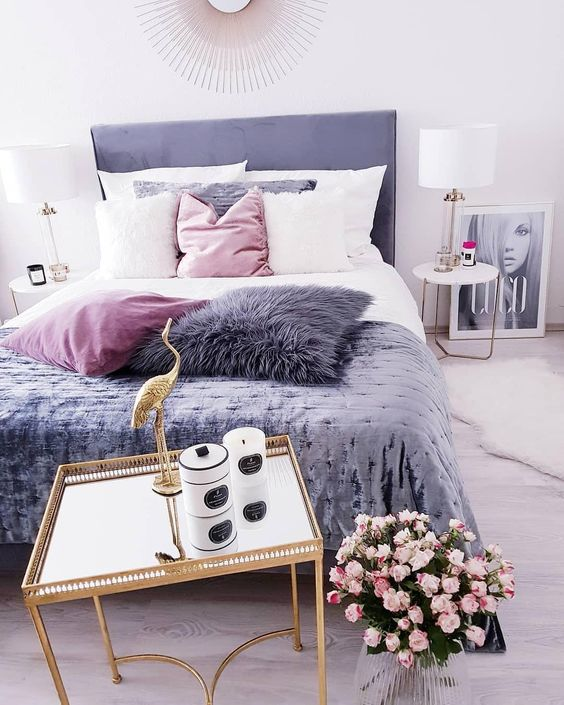 a cool feminine bedroom with a purple bed, a gold nightstand with candles, pink blooms, pink, white and purple pillows