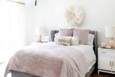 a cool girlish bedroom with a grey bed, pink and neutral bedding, a blush rug, a beaded chandelier and touches of gold