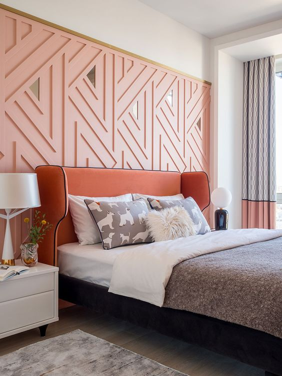 a cool modern feminine bedroom with apink geometric wall, a terracotta bed, white nightstands, color block curtains and printed bedding