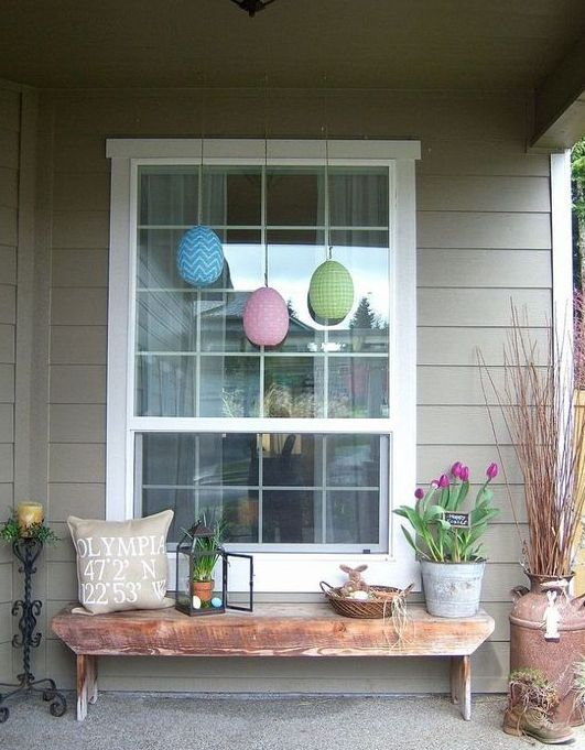 a cozy Easter front porch with potted tulips, colorful eggs, a lantern with greenery and eggs and a bunny