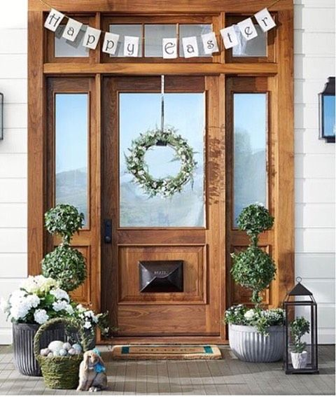 a cozy Easter porch with a bunting, greenery topiaries, blooms in baskets and lanterns and eggs in moss baskets