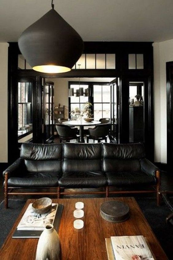 a cozy dark manly room with a black elather sofa, a wooden coffee table, a matte black pendant lamp and candles