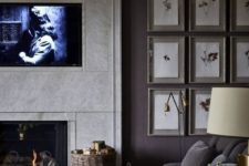 a cozy masculine livign room with a gallery wall, grey furniture, a basket with firewood, a fireplace and some lamps