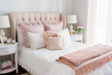 a cute and sweet feminine bedroom with grey walls, a neutral bed with pink ruffled bedding, a pink rug and white nightstands