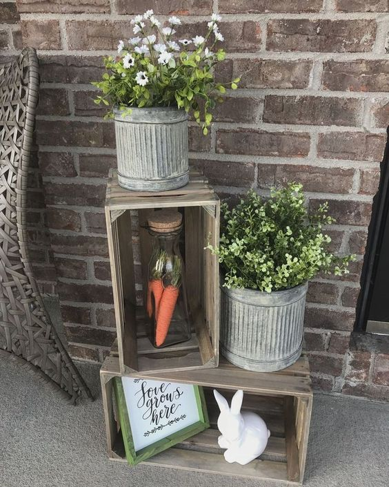 a cute rustic spring decoration of crates, a bunny, a sign, some potted greenery and flwoers and carrots in a jar