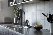 a dark and moody kitchen with dark stained furniture, stone countertops, a grey tile backsplash for a masculine feel