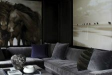 a dark living room with grey furniture, oversized artworks, an upholstered ottoman and a rug