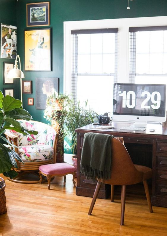 a deep green wall, a bright printed chair and some potted greenery make the home office spring-filled