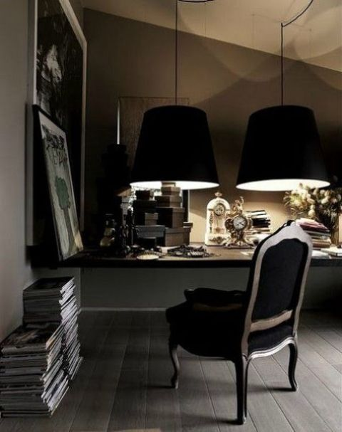 a dramatic masculine home office with a floating desk, a refined chair, large black lamps and stacks of books