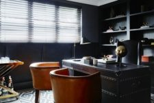 a gorgeous masculine home office with black walls, a black metal desk with amber leather chairs and shiny metallic touches
