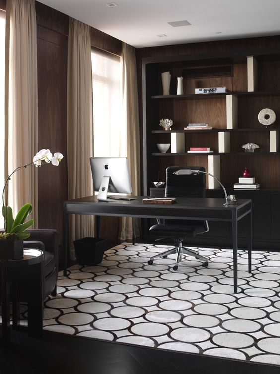 a laconic home office with open shelving, an elegant desk, a printed rug, neutral curtains and a potted orchid