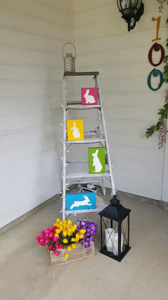 a ladder with colorful bunnies, a lantern with candles and colorful potted tulips in a wooden planter