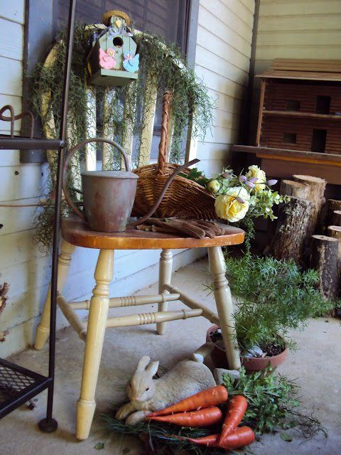 a lovely porch decoration with much greenery, carrots, bird houses and a basket with flowers