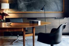 a luxurious home office with an oval wooden desk, black leather chairs and an oversized dark artwork