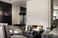 a luxurious masculine living room with white walls, grey and black furniture, a fireplace, lamps and artworks