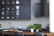 a masculine kitchen with graphite grey cabinets, a wooden kitchen island, black leather stools and a black hood