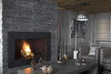 a masculine living room with a stone clad fireplace, wooden tables, a faux fur rug, upholstered furniture and lamps