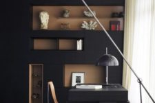a mid-century modenr home office with a black wall, a rich stained niches, a black desk and stylish lamps