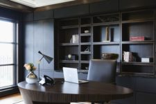 a minimalist and refined home office with a black built-in shelving unit, a sculptural oval desk of rich stained wood, a bold chandelier
