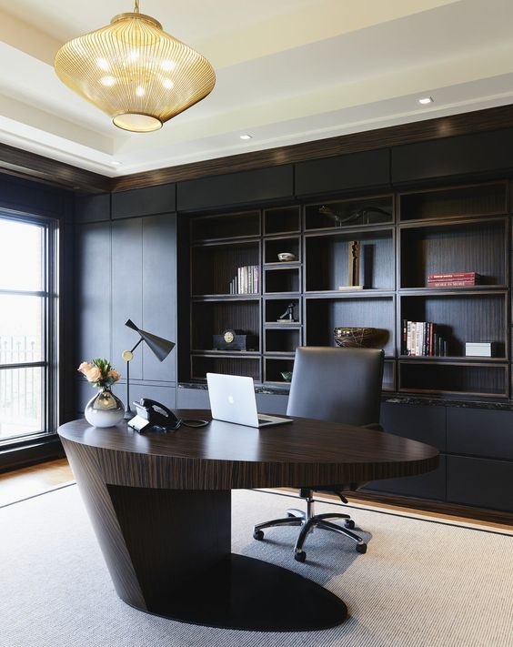 a minimalist and refined home office with a black built in shelving unit, a sculptural oval desk of rich stained wood, a bold chandelier