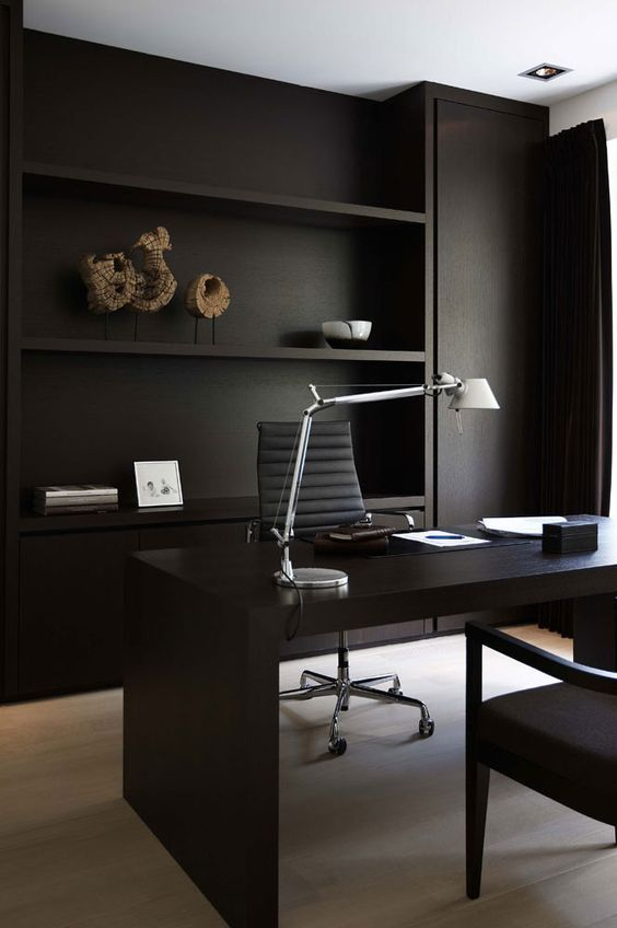 a minimalist home office with matte black walls and built-in shelves, a black desk and comfortable chairs