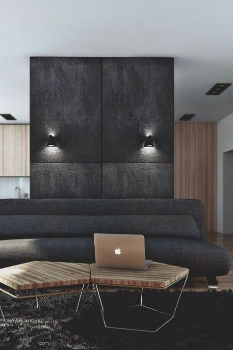 a minimalist masculine living room with a dark wall and sofa, a hex coffee table and lights