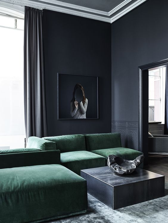 a minimalist masculine living room with graphite grey walls, an emerald velvet sofa and a sleek grey table