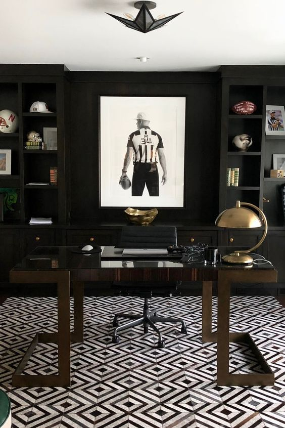 a modenr moody masculine home office with blakc built in shelves, a dark stained desk, a sport themed artwork plus shiny metal accents
