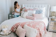a modern feminine bedroom with a white upholstered bed, mirror nightstands, a grey bench, pink and white bedding and floral artworks