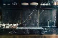 a moody and chic masculine kitchen with a black marble backsplash and countertops, rich-stained wooden furniture