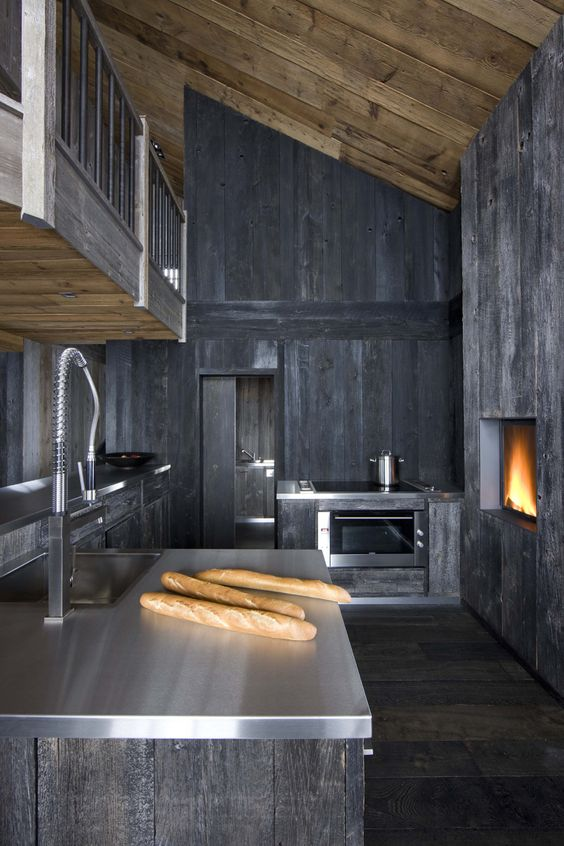a moody and rough grey kitchen of wood with metal countertops, a hearth and wooden walls for a rustic feel