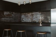 a moody black kitchen with sleek cabinets, a rusty metal backsplash, pendant lamps and tall stools