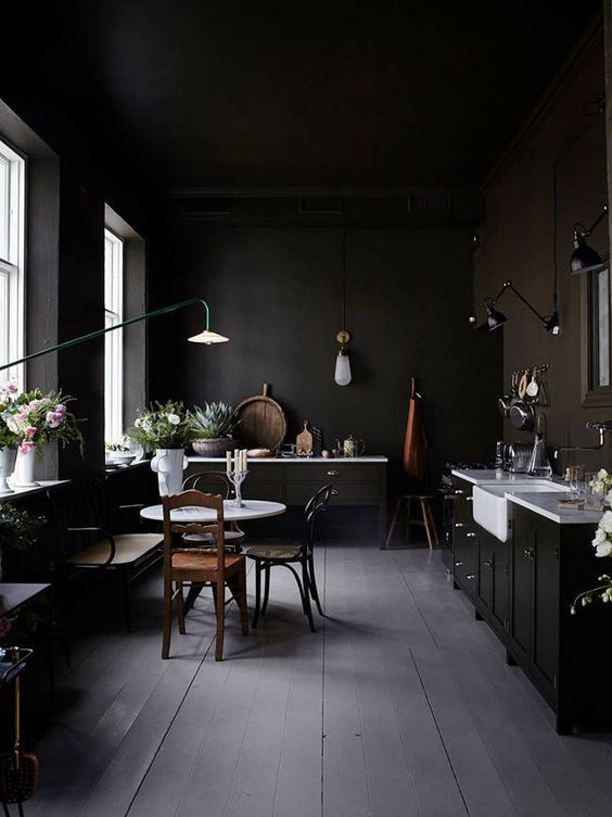 a moody vintage kitchen with white countertops, wall lamps and floral arrangements