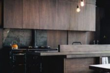 a moody wooden kitchen with pendant lamps, a metal backsplash and a hearth for more coziness
