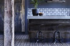 a navy kitchen with blue walls, a rug, printed tiles, a rough kitchen island with a stone countertop looks chic