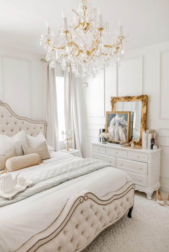 a neutral Versaille inspired bedroom with refined furniture, a crystal chandelier, gold framed art and mirrors and layered bedding