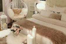 a neutral and blush feminine bedroom with a white upholstered bed, a furry bench, a suspended chair and a feather chandelier