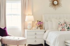 a neutral feminine bedroom with a white upholstered bed, white nightstands, a blush couch and a purple pillow and blush curtains