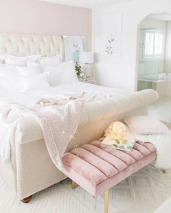 a pretty girlish bedroom done in white and light pink, with an upholstered bed and a pink bench, white bedding and lights