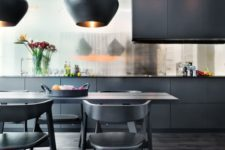 a refined and elegant black kitchen with a shiny backsplash, sleek cabinets, a dining set in black and catchy pendant lamps