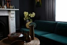 a refined dark masculine room with dark walls, a forest green sofa, a fireplace and a wicker coffee table