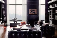 a refined living room with black leather furniture, large book shelf units, neutral curtains and some coffee tables