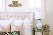 a romantic and feminine bedroom with a neutral upholstered bed, blush and white bedding, a crystal chandelier and a mirror nightstand