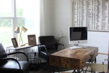 a rustic home office with a stained desk on metal legs, leather chairs, an animal skin rug and a typography artwork