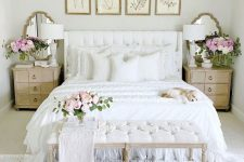 a shabby chic feminine bedroom with a white bed and bench, botanical artworks, wooden nightstands, a chic chandelier and blooms