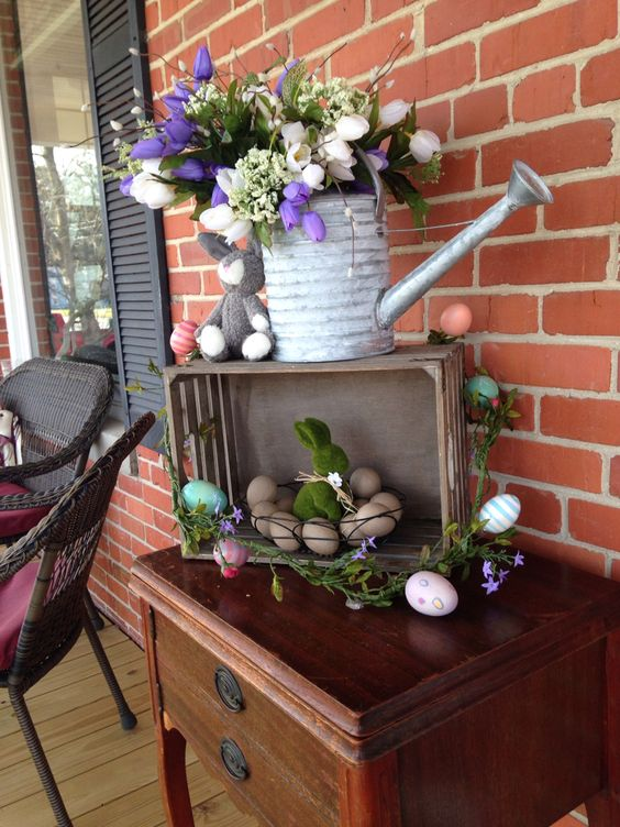a simple Easter decoration of a crate with colorful eggs, a watering can with a spring bloom arrangement and bunnies