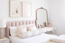 a simple feminine bedroom with a blush bed, white nightstands, a mirror in a brass frame and cute artworks
