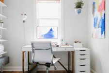 a single bright artwork and soem greenery in a pot make the home office bright and spring-inspired