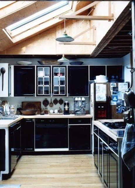 a sleek and refined black kitchen with white countertops and framing plus metal pendant lamps
